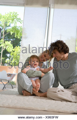 Parents laugh with baby on floor - Stock Photo