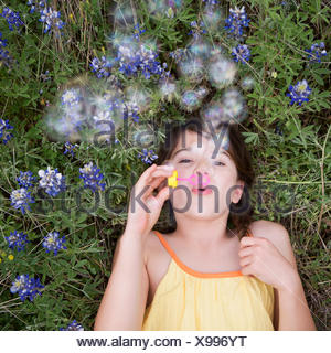 A girl lying on her back blowing bubbles in the air. - Stock Photo