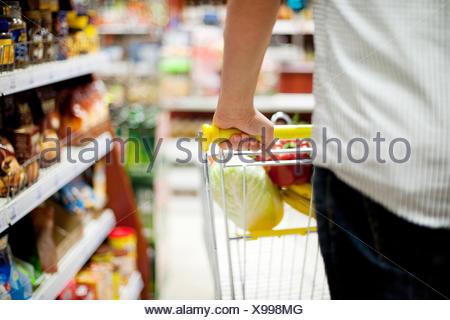Man pushing shopping trolley Debica, Poland - Stock Photo