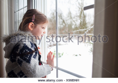 Young girl looking out of window at garden in snow - Stock Photo