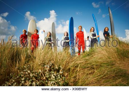 Portrait of group of surfers standing on beach, holding surfboards - Stock Photo