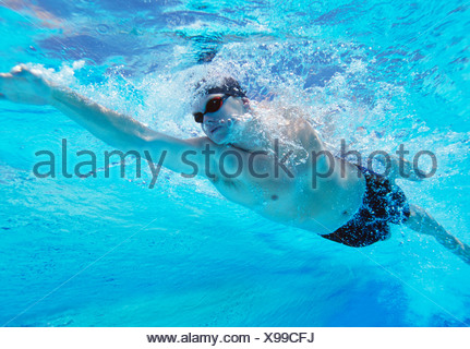 Underwater shot of professional male thlete swimming in pool - Stock Photo