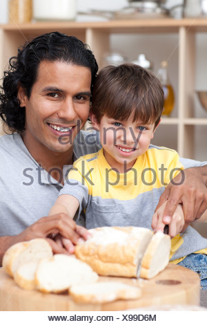 Smiling father helping his son cut some bread - Stock Photo