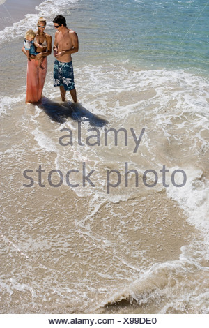 Two generation family standing in surf at beach mother carrying daughter 2 3 elevated view - Stock Photo