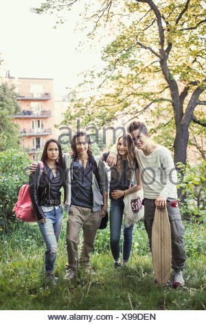 Portrait of confident high school students standing together in park - Stock Photo