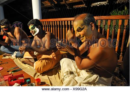 Kathakali performers during making up before a show at the Kumarakom Lake Resort hotel, Kerala state, South India, Asia. - Stock Photo