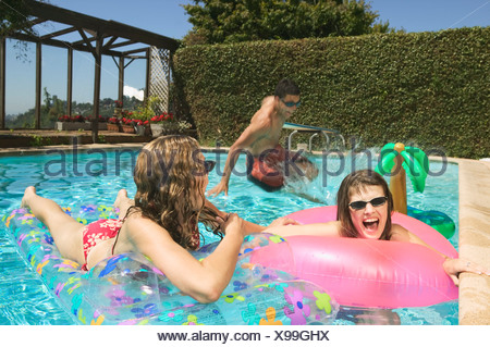 A group of teenage kids playing in a pool - Stock Photo