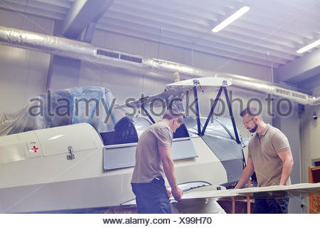 Male engineers assembling airplane in hangar - Stock Photo