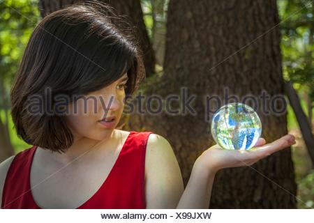 Young woman, standing by a tree in a park, holding a crystal ball. - Stock Photo