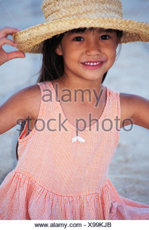 Close-Up Of A Little Girl In Peach Dress, With Straw Hat, Smiling - Stock Photo