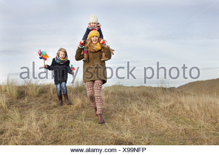 Smiling mid adult woman with daughter and son at coast - Stock Photo