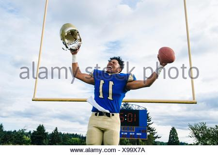 Teenage American football player celebrating on soccer pitch - Stock Photo