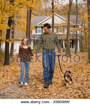 Father and daughter walking dog in woods - Stock Photo