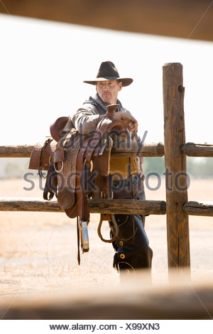 A rancher leaning against a saddle on a fence - Stock Photo