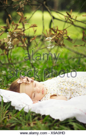 Side View Of A Cute Baby Girl Sleeping On Grassland - Stock Photo