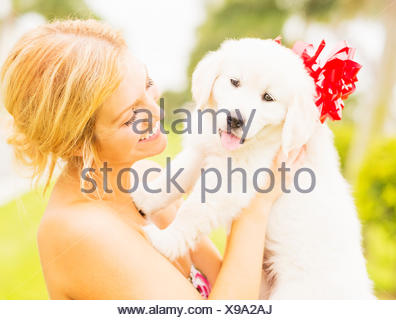USA, Florida, Jupiter, Young woman holding white puppy with ribbon bow - Stock Photo