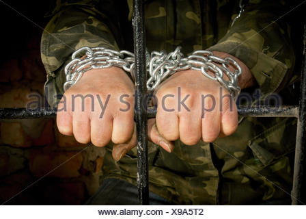 Man with hands tied up with chain - Stock Photo