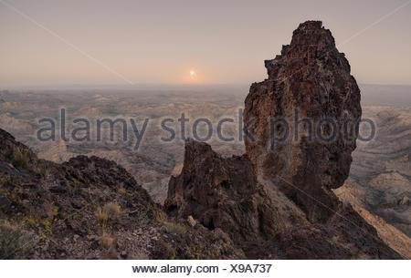 USA, Arizona, Kofa National Wildlife Refuge, Full Moon Rising from Castle Dome - Stock Photo