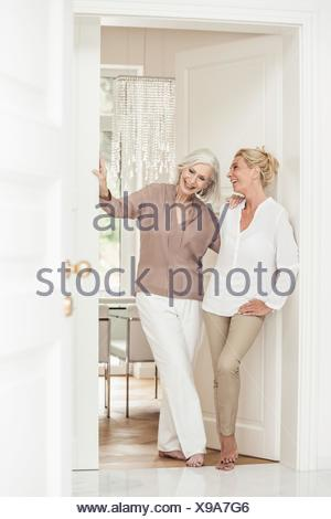 Mother and daughter standing together at home, laughing - Stock Photo