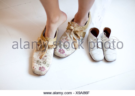 Woman putting on floral shoes - Stock Photo