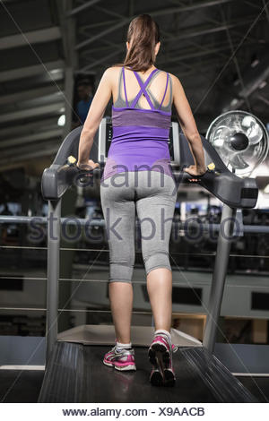 Rear view of pregnant woman on tredmill - Stock Photo