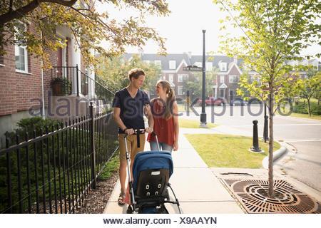 Couple pushing baby stroller on sunny neighborhood sidewalk - Stock Photo