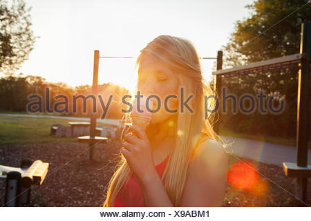 Young woman eating ice cream cone in park at sunset - Stock Photo