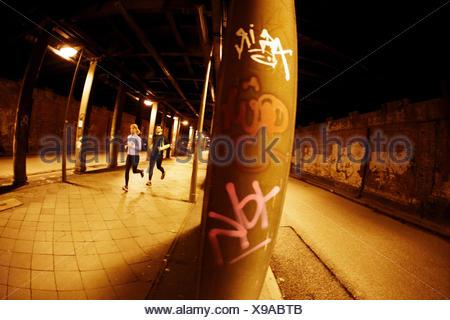 A couple runs through a dark tunnel in downtown Hamburg, Germany. - Stock Photo
