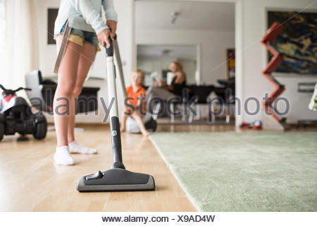 Low section of girl cleaning floor with vacuum cleaner at home - Stock Photo