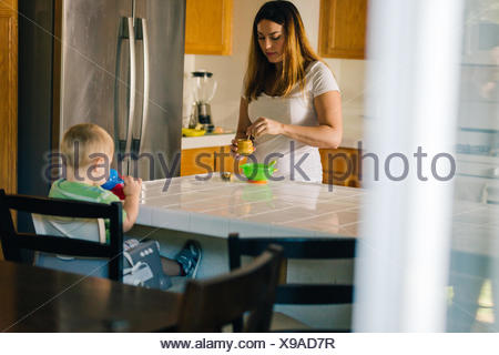 Mother and young son at kitchen table, mother preparing food, son drinking from sippy cup - Stock Photo
