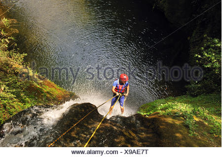 young woman rappelling while Canyoning between Pokhara and  Kathmandu, Nepal - Stock Photo