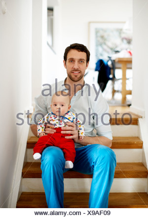 Portrait of father with baby sitting on floor - Stock Photo