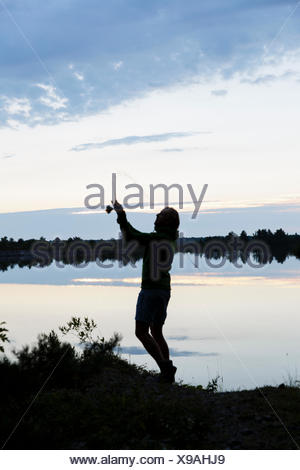 Sweden, Gotland, Farosund, Bastetrask, Silhouette of man fishing on river - Stock Photo