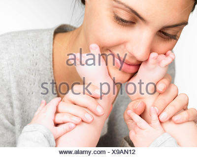 Mother playing with her baby's feet - Stock Photo