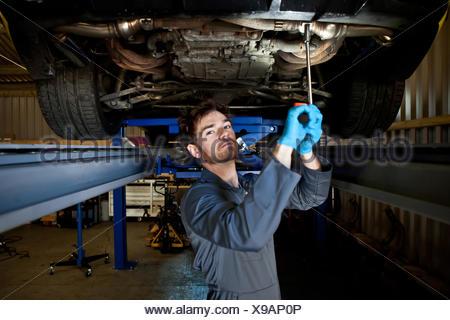 Male mechanic doing maintenance under car - Stock Photo
