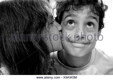 Girl kissing boy on the cheek - Stock Photo