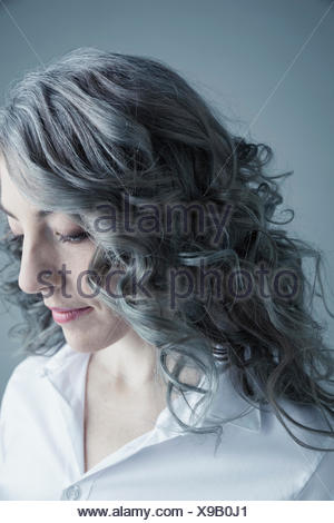 Portrait serious Caucasian mid adult woman with curly gray hair and nose ring looking down - Stock Photo
