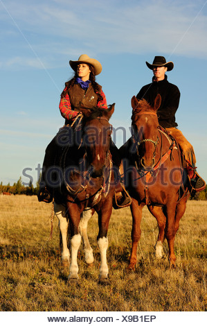 Cowboy and cowgirl riding horses, looking into the distance, Saskatchewan, Canada, North America Stock Photo