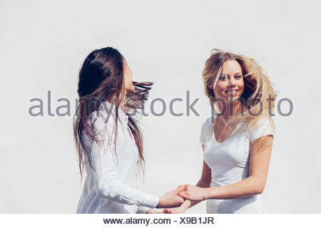 Two young women wearing white clothes tossing her hair in front of white background - Stock Photo