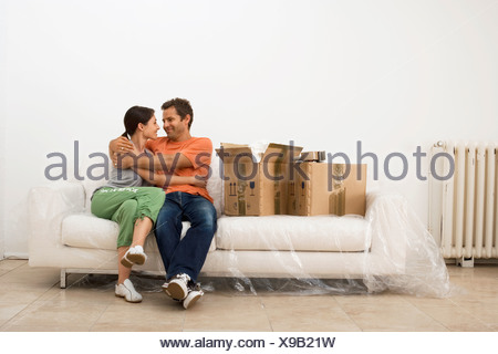 Couple moving house embracing on white sofa wrapped in plastic sheet beside boxes smiling - Stock Photo