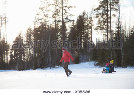 Father pulling sons along on sledge in snow covered landscape - Stock Photo