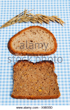 Two slices of bread on blue and white tablecloth, with oats - Stock Photo