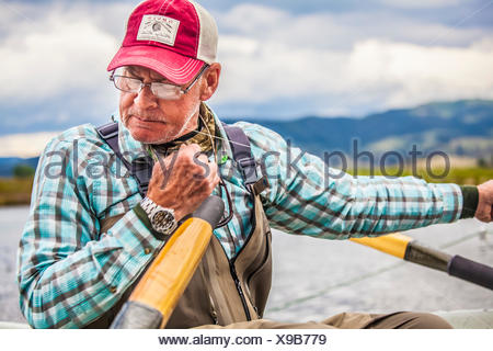 A fly fisherman changes flies while on a drift boat. - Stock Photo