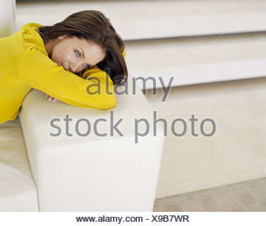 A woman resting her head on a couch arm - Stock Photo