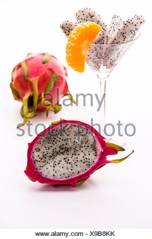 A longitudinal section of a pitaya. Its white pulp is covered with a vibrant violet skin. Its flavor is in harmony with the aroma of the mandarine. - Stock Photo