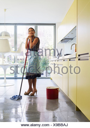 Young woman daydreaming, holding mop - Stock Photo