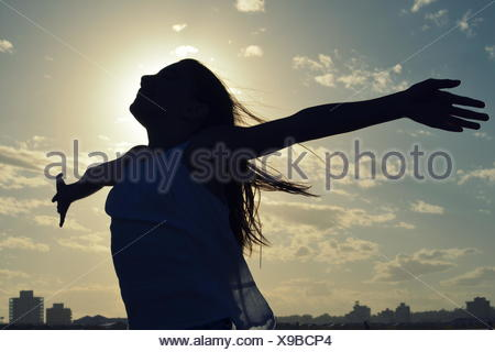 Silhouette of a girl standing with outstretched arms - Stock Photo