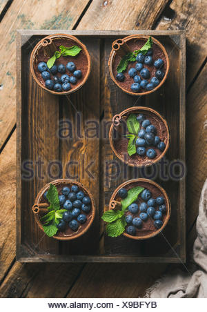 Homemade Tiramisu dessert in glasses with cinnamon sticks, mint leaves and fresh blueberries in wooden tray over rustic wooden b - Stock Photo