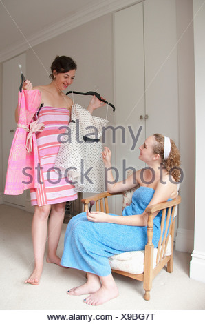 Teenage girls picking out dresses - Stock Photo