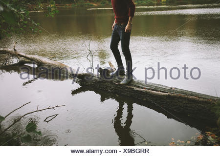 Cropped shot of young man standing on tree trunk in river - Stock Photo
